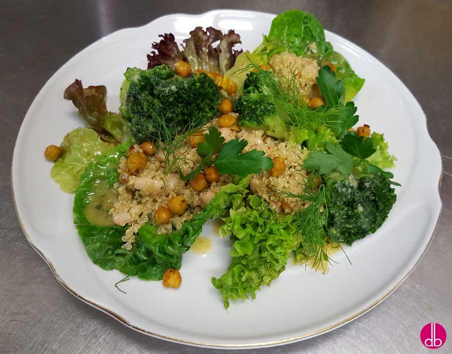 Quinoa salat auf frischem Blattsalat anrichten, mit frischen Kräutern garnieren und die gebackenen Kichererbsen darüber geben.